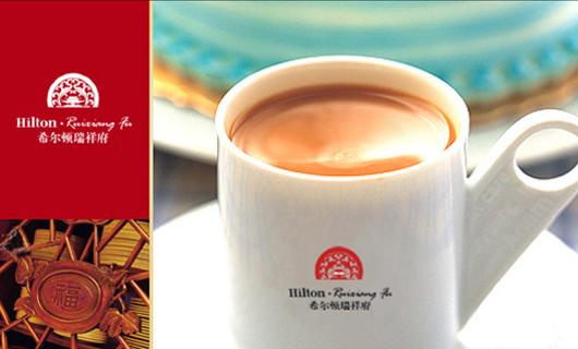 """希尔顿瑞祥府的VI标识采用了图形与文字结合的方式。文字采用的是黑色字体,直接表明公司的名称,磅礴大气。图形采用了极具中国文化的""""中国红""""。红色在中国多用来象征喜庆的氛围,也寓意生意做得红红火火。图形内部的建筑标志是中国首都北京天安门,环绕着天安门的是红色祥云,同时对称着的祥云又像是两条飞舞的龙,整个图形的设计又像是中国的剪纸画,所有的元素中都包含着中国特色。希尔顿瑞祥府形成了自己特有的中国特色文化。无论是来自中国的家乡友人,还是来自海外的异国朋友,到这里都会深深的感受到中国文化,有"""